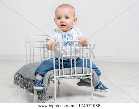 cute curious baby boy sitting on a little bed in white room