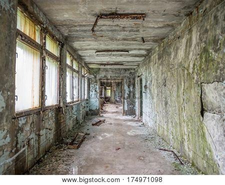 abandoned ruined corridor with debris in Pripyat school