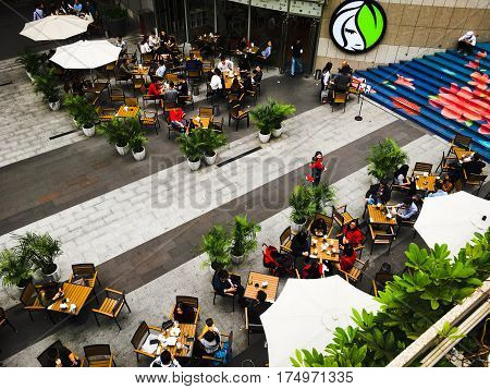 Shenzhen. China-March 06,2017: Many relaxed people sitting in the the street open air cafe. Top view close up.