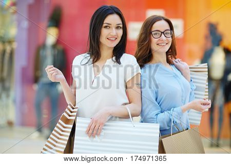 Young friendly shoppers with paperbags