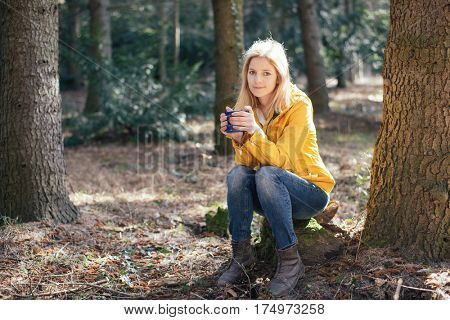 Cute blonde traveler woman resting in forest and drinking hot coffee or tee from a vintage mug