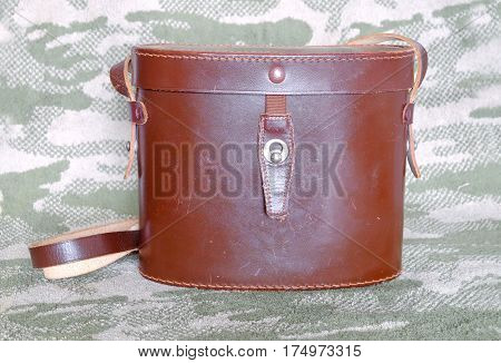 Vintage brown color closed hard leather carry case for binoculars on camouflage background front view indoor closeup