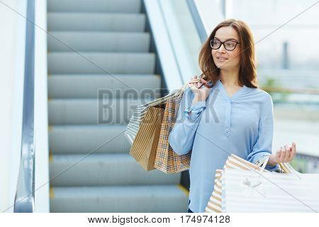 Woman with shopping-bags looking sideways by escalator