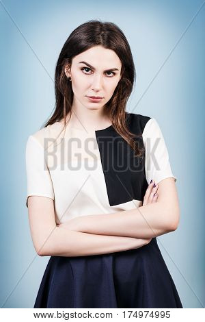 Angry young woman with crossed hands over blue background