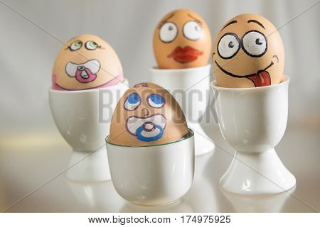 Happy egg face family in eggcup on white