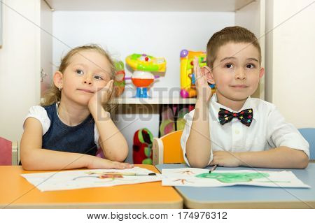 Adorable children boy and girl draws a brush and paints in nursery room. Kid in kindergarten in Montessori preschool class