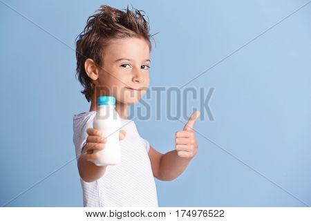 Cute kid holding plastic bottle of milk on blue background