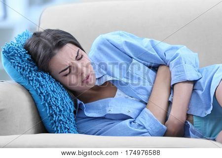 Young woman suffering from abdominal pain while lying on sofa at home. Gynecology concept