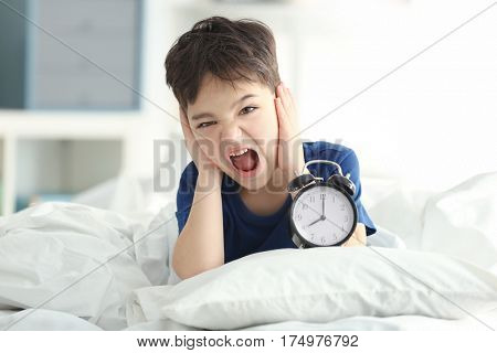 Cute little boy with ringing alarm clock in bed