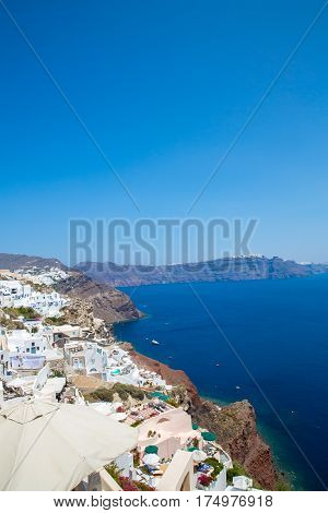 View of Fira town - Santorini islandCreteGreece. White concrete staircases leading down to beautiful bay with clear blue sky and sea