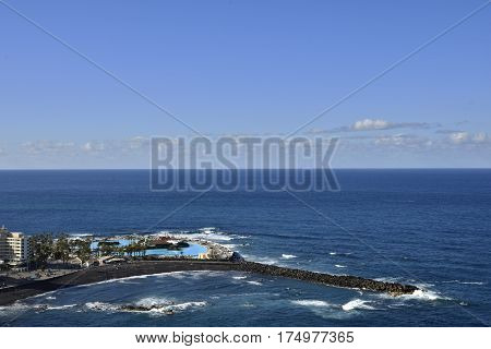 Resort and a beach with black lava sand and a pir as protection against waveshorizon and blue sky in background picture from Puerto de la Cruz Tenerife Spain.