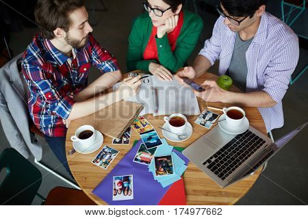 Top view of round meeting table with group of young creative people wearing business casual clothes collaborating at it and discussing work drinking tea
