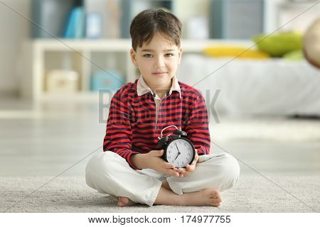 Cute little boy with alarm clock sitting on floor at home