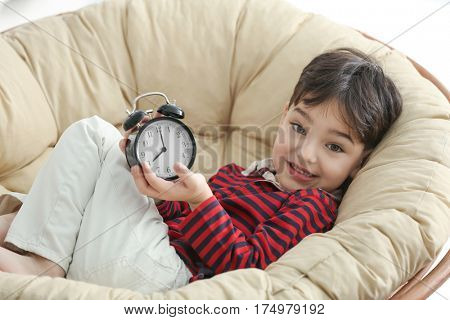 Cute little boy with alarm clock on lounge at home