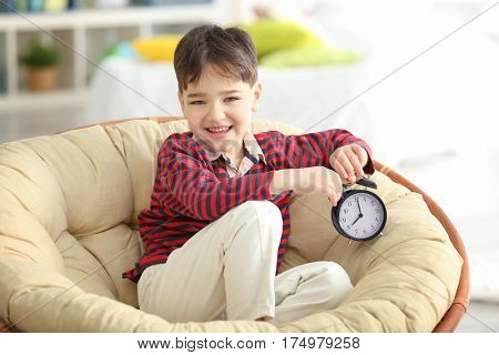 Cute little boy with alarm clock sitting on lounge at home