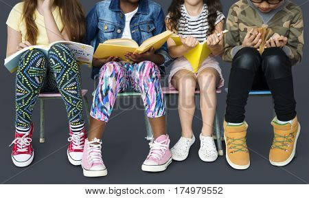 Diverse group of kids sitting in a row reading books