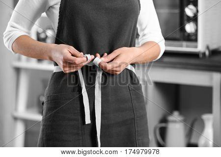 Closeup of woman tying apron on kitchen