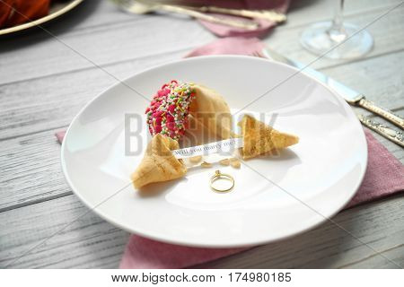 Fortune cookies with golden ring on wooden table