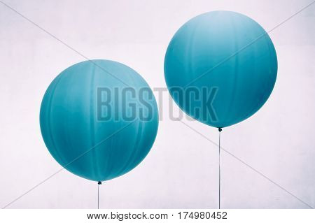 Two blue inflated balloons on white background