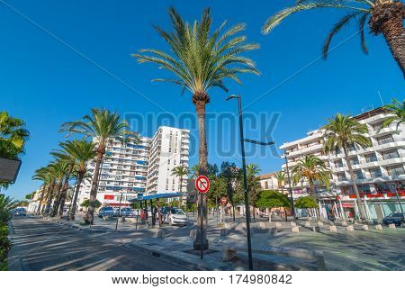 Sant Antoni De Portmany, Ibiza, November 6th, 2013:   Tourism in Spain.  Bright morning sunshine on town square.  Palm tree lined pedestrian park & fountain.  Hotels in background.  People wait for a taxi at a stand in the square.