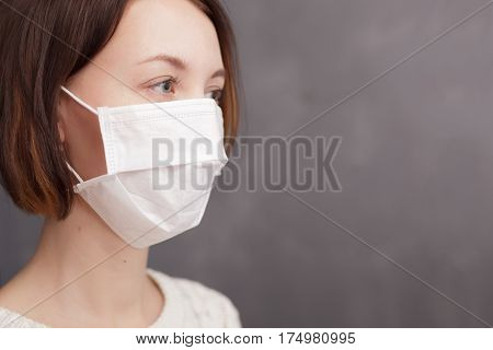 Girl in medical disposable mask looking at the camera. Protection against viruses and bacteria during the flu epidemic