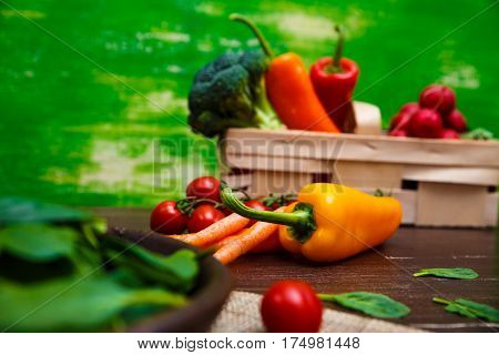 Sweet pepper, brocoli and cherry tomatoes. Brocoli and red radish. Natural raw vegetables. Organic bio food on rustic wooden table.