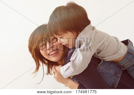 Japanese mother hugs her son they laugh and smile. Warm family relations.