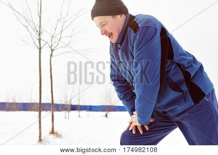 Man warming up before running in the winter on snow