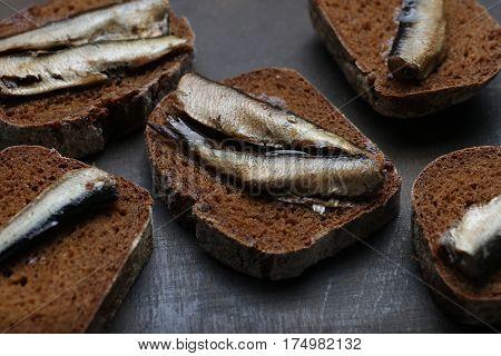 Snacks With Sardines On Black Rye Sliced Bread. Riga Traditional Delicious Dish. Smoked Sprats On Da
