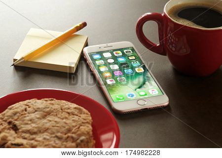 Koszalin, Poland - March 07, 2017: Pink iPhone 7 on stone table. Devices displaying the applications on the home screen. The iPhone 7 is smart phone with multi touch screen produced by Apple Computer