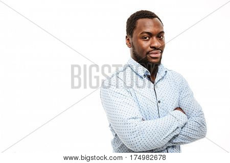 Image of handsome young african man dressed in shirt standing isolated over white background. Arms crossed.