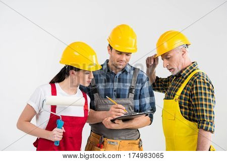 Group of professional male and female construction workers looking at clipboard