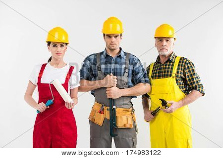 Professional construction workers holding tools and looking at camera
