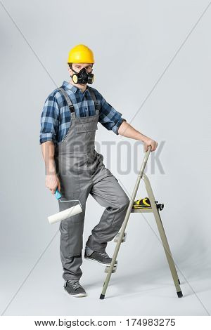 Workman in protective workwear standing on ladder with paint roller