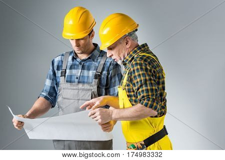 Two professional male engineers working with blueprint on grey