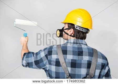 Male construction worker in protective workwear with paint roller on grey