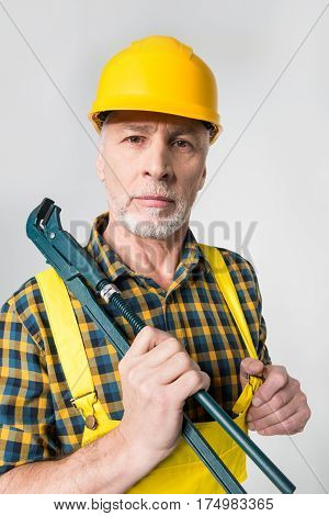 Mature workman in hard hat holding pipe wrench on grey