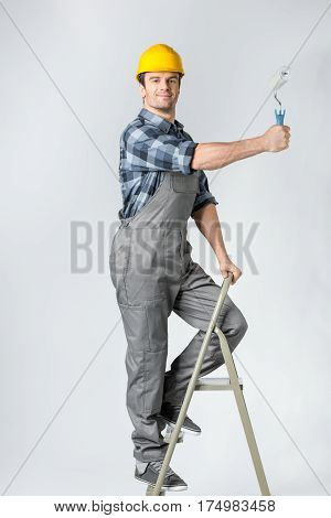 Smiling workman standing on ladder and painting wall with roller