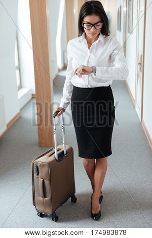 Full length portrait of a serious young business woman in skirt walking with suitcase along hotel lobby and looking at her wristwatch