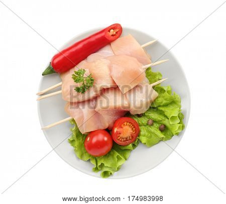 Raw chicken meat with vegetables on white background