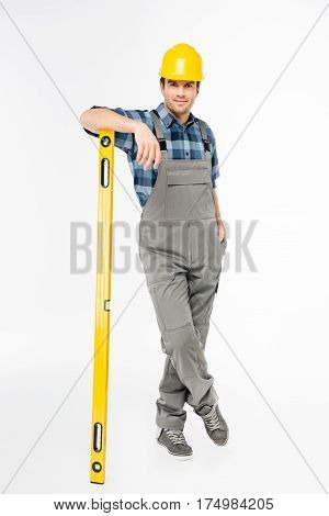 Full length portrait of workman with level tool smiling at camera