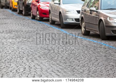 Cobblestone road with row of colorful cars at parking zone on the street behind a blue diagonal line (copy space)