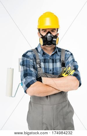 Workman in protective workwear holding paint roller and looking at camera