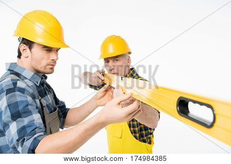 Two serious workmen in hard hats working with level tool on white