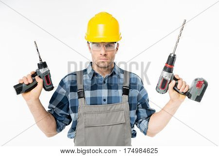 Serious workman in protective workwear holding electric drills
