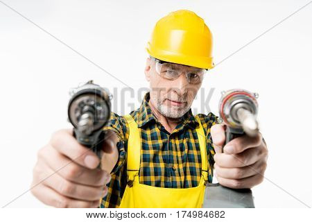 Close-up view of mature workman holding electric drills and looking at camera
