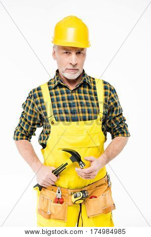 Mature workman in hard hat holding hammer and looking at camera on white