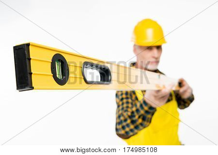 Mature workman in yellow hard hat holding level tool on white