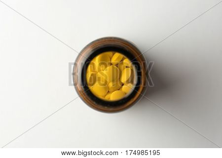 Medicine bottle or jar of pills, shot from above. On natural white background.