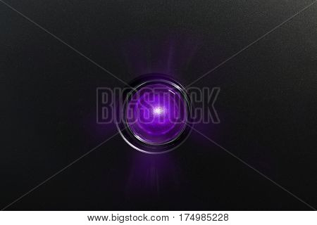 Purple glowing status indicator, warning lamp or button, on black panel.